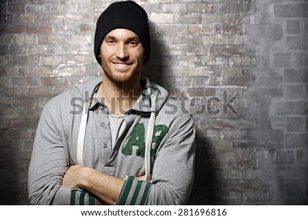 Portrait of happy young casual man standing over brick wall - stock photo