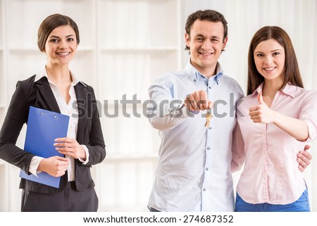 Portrait of happy young couple are holding keys and female realtor in a new flat.