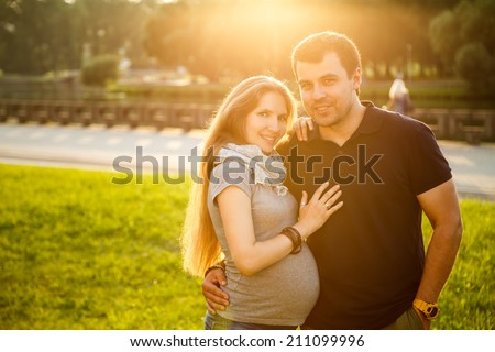 Portrait of Happy Young Couple Expecting Baby on Green Nature Background. Warm Color Toned Photo with Lens Flare at Sunset. Romantic Pregnancy Concept. - stock photo