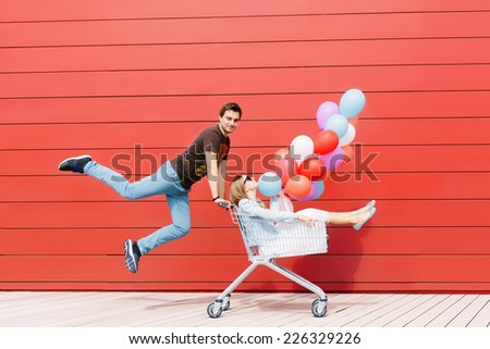 Portrait of happy young couple having fun. Girl sitting in shopping cart and keeping color balloons in hand. Man jumping. Red background. Outdoors - stock photo