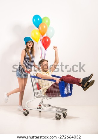 Portrait of happy young couple having fun. Man sitting in shopping cart and keeping color balloons in hand. Woman rolling trolley.