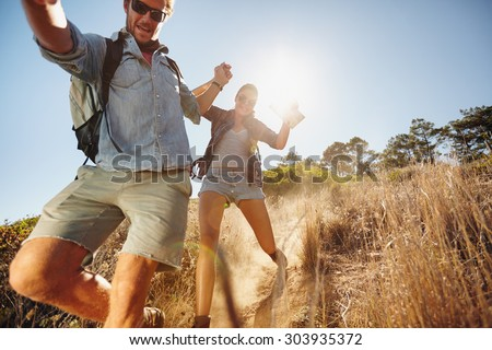 Portrait of happy young couple having fun on their hiking trip, sliding down the mountain trail. Caucasian hiker couple enjoying themselves on summer vacation. - stock photo