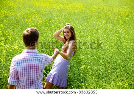 Portrait of happy young couple holding by hands in flower field - stock photo