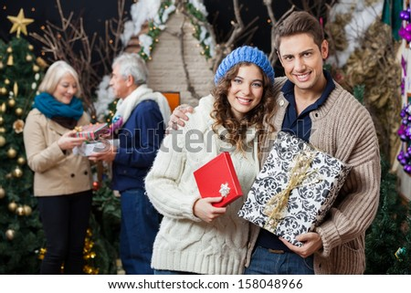 Portrait of happy young couple holding Christmas presents with parents standing in background at store - stock photo