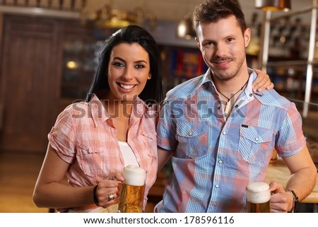 Portrait of happy young couple holding glass of beer in pub, smiling. - stock photo