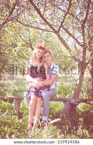 Portrait of happy young couple in bohemian style hugging on garden bench on green outdoors background - stock photo
