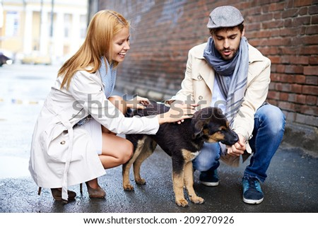 Portrait of happy young couple in stylish clothes feeding dog outside - stock photo