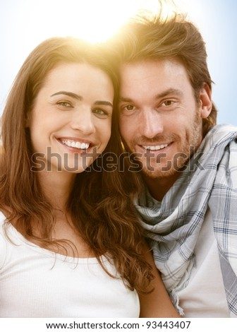 Portrait of happy young couple in summer sunlight, looking at camera, smiling.? - stock photo