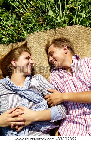Portrait of happy young couple lying on straw rug outside - stock photo