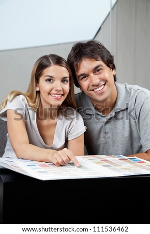 Portrait of happy young couple sitting together with color swatch chart