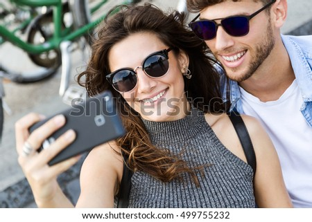 Portrait of happy young couple using mobile phone in the street.