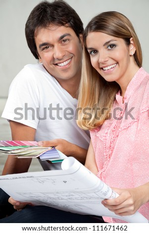 Portrait of happy young couple with blueprint and color swatches