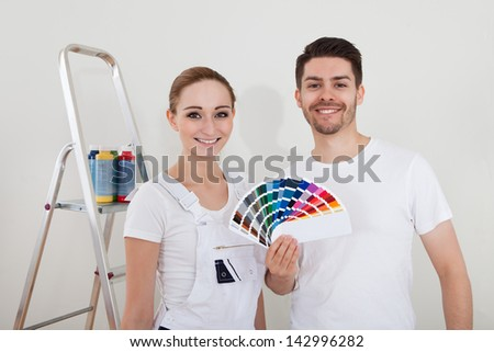 Portrait Of Happy Young Couple With Color Samples - stock photo