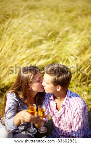 Portrait of happy young couple with flutes kissing outside - stock photo