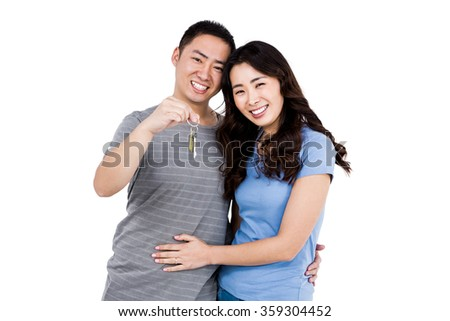 Portrait of happy young couple with keys against white background