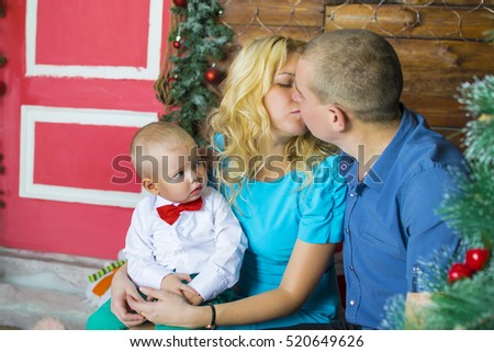 Portrait of happy young family at christmas morning, little boy having lollipop.