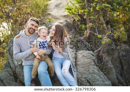 Portrait of happy young family in a sunny day - stock photo