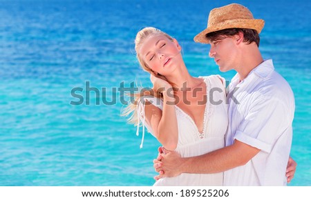Portrait of happy young family in love, hugging on the beach, romantic relationship, summer vacation, gentle loving feelings concept - stock photo