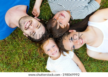 Portrait of happy young Family lying on grass
