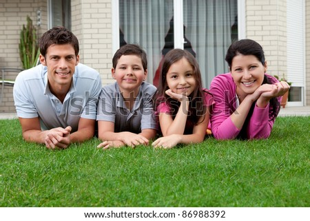 Portrait of happy young family lying on grass outside their house