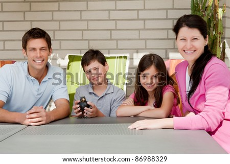 Portrait of happy young family sitting together in backyard - stock photo