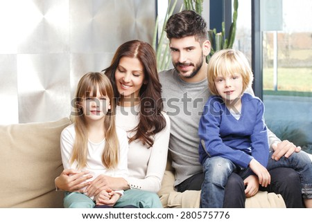 Portrait of happy young family with two kids sitting at sofa and smiling.  - stock photo