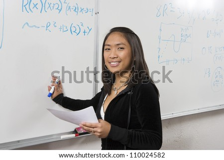 Portrait of happy young female student holding marker and paper in front of whiteboard