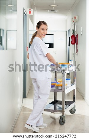 Portrait of happy young female technician pushing medical cart in hospital hallway - stock photo