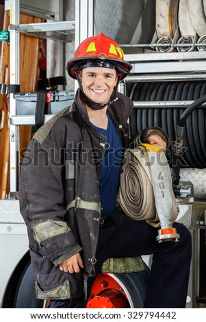 Portrait of happy young fireman holding hose while standing by truck at fire station