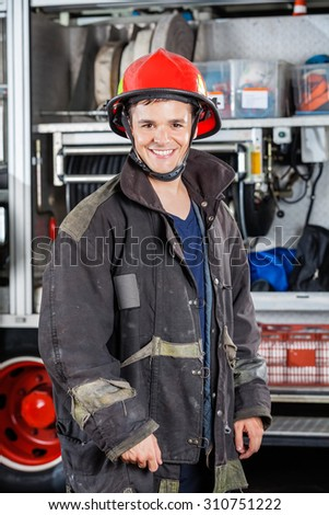 Portrait of happy young fireman standing against truck at fire station - stock photo