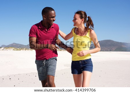 Portrait of happy young fitness couple walking together on beach - stock photo