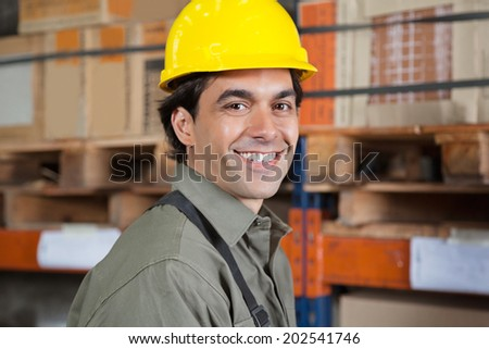 Portrait of happy young foreman in hardhat at warehouse - stock photo