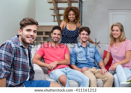 Portrait of happy young friends sitting on sofa in living room
