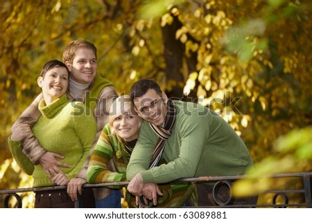 Portrait of happy young friends standing in autumn park, leaning to railing, smiling.? - stock photo