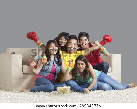 Portrait of happy young friends watching a boxing match together at home - stock photo