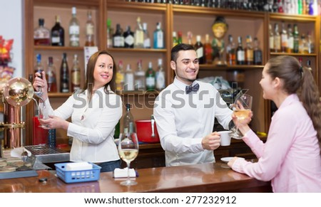 Portrait of happy young girl flirting with handsome smiling barman in bar - stock photo