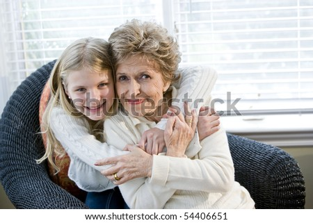 Portrait of happy young girl hugging grandmother at home - stock photo