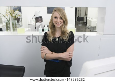 Portrait of happy young hairstylist standing arms crossed at reception in salon - stock photo