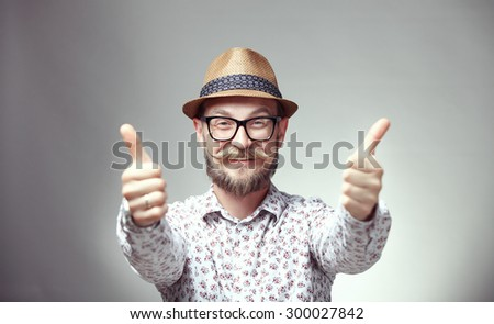 Portrait of happy young hipster thumbing up, isolated on grey background - stock photo