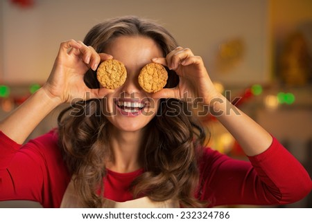 Portrait of happy young housewife holding cookies in front of eyes - stock photo