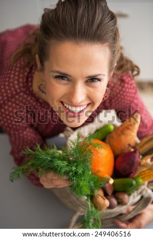 Portrait of happy young housewife with shopping bag of fresh vegetables from local market - stock photo
