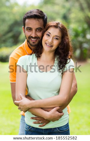 portrait of happy young indian couple enjoying summer day outdoors - stock photo