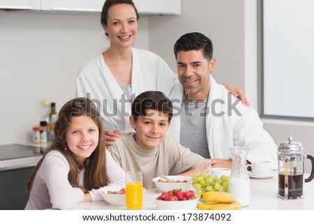 Portrait of happy young kids enjoying breakfast with parents in the kitchen - stock photo