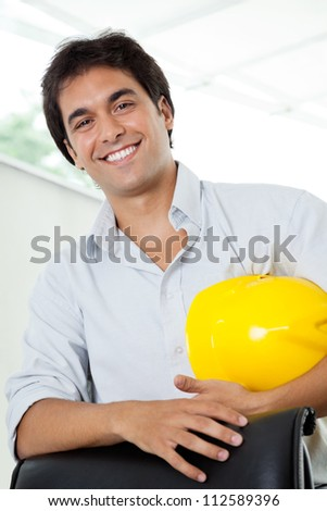Portrait of happy young male architect holding yellow hardhat while standing by office chair
