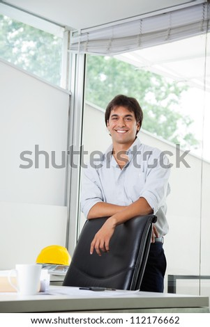Portrait of happy young male architect standing by office chair