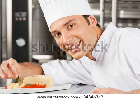 Portrait of happy young male chef garnishing dish in commercial kitchen