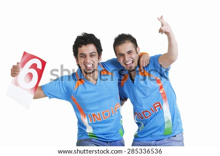 Portrait of happy young male friends in jerseys cheering over white background - stock photo