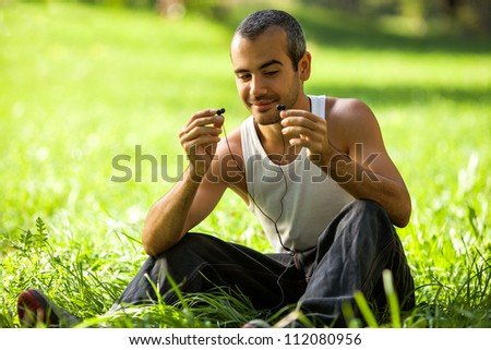 Portrait of happy young male listening to music on headphone while lying in a park - Outdoor - stock photo