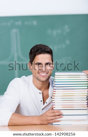 Portrait of happy young male student with stacked books at desk in classroom