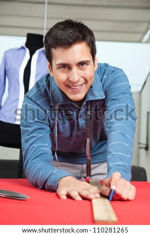 Portrait of happy young male tailor drawing line on a red fabric with chalk
